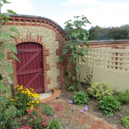 Part of our cottage garden. Self-built brick and cobbled wall with false doorway feature flanked by sunflowers. Brick path and wooden screen keeps it intimate. Peter French